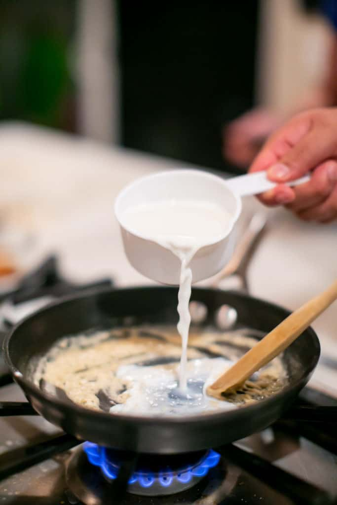 Pouring a cup of cream into a rue in the pan