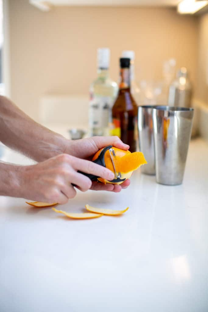 Man peeling an orange on top of a white counter