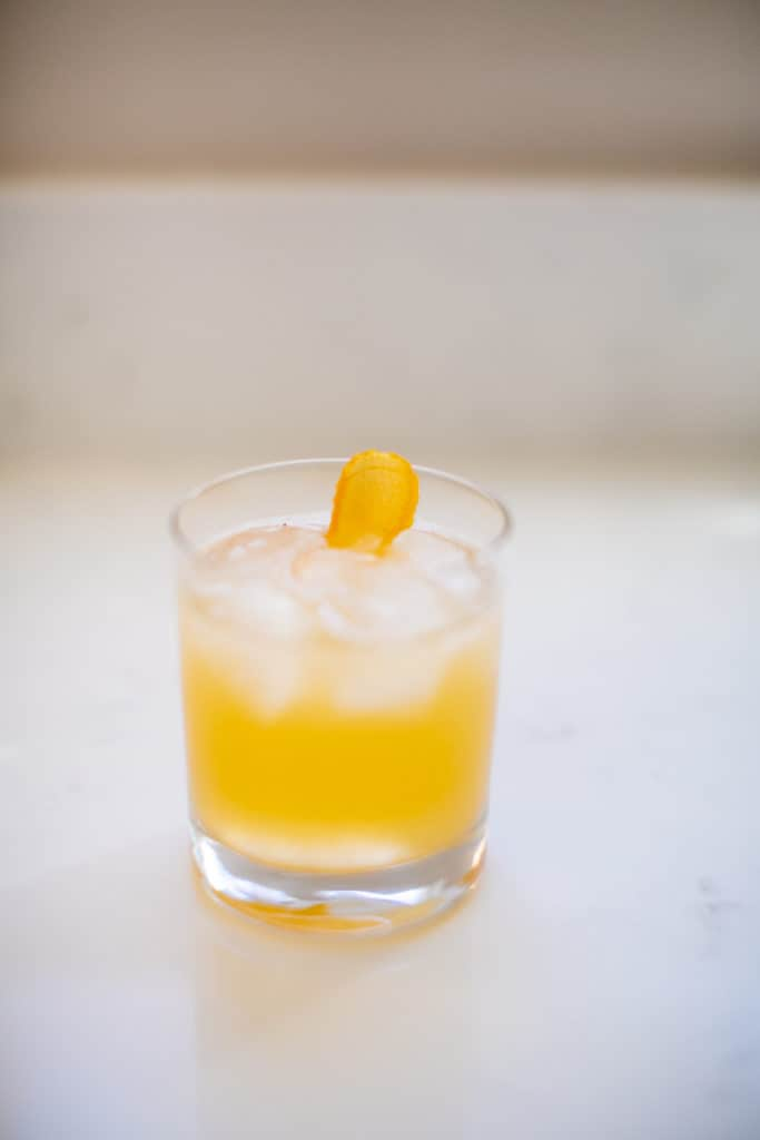 An orange cocktail drink in a small glass
