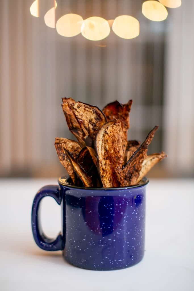 Close photo of eggplant chips in a blue mug