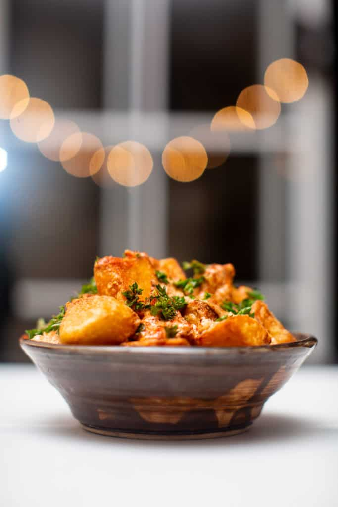 Fried patatas bravas tapas served on a bowl and topped with parsley