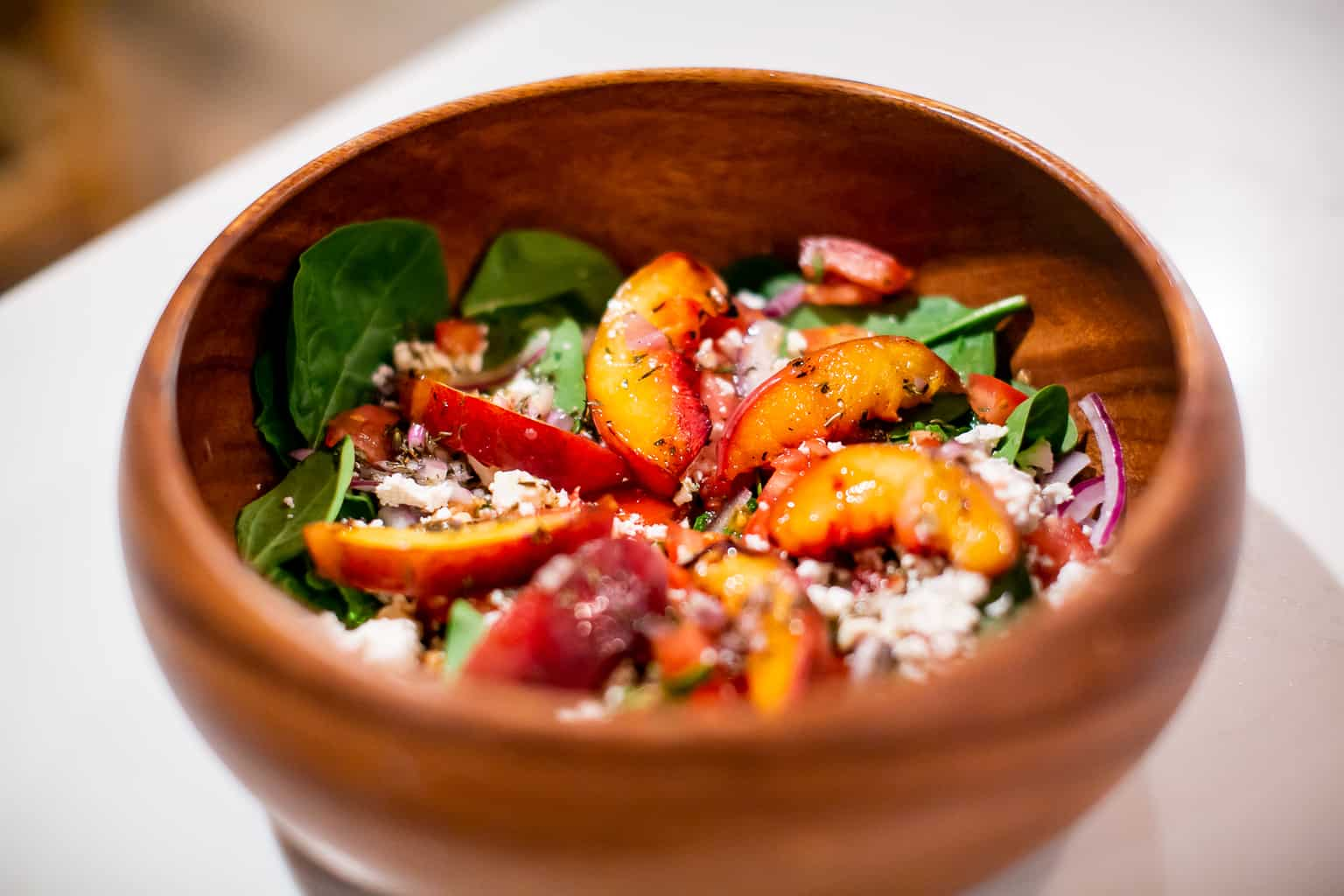 Grilled peach salad served on a wooden bowl