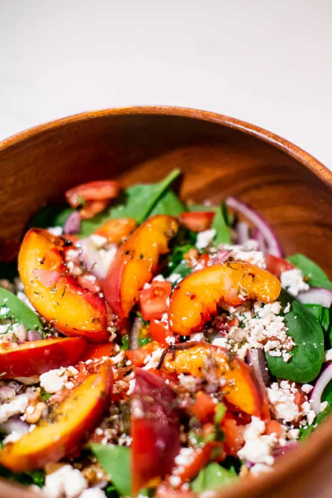 Close up of grilled peach salad on a wooden bowl
