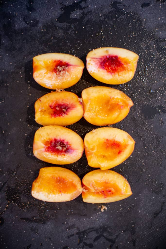 Sliced peaches on a black tray