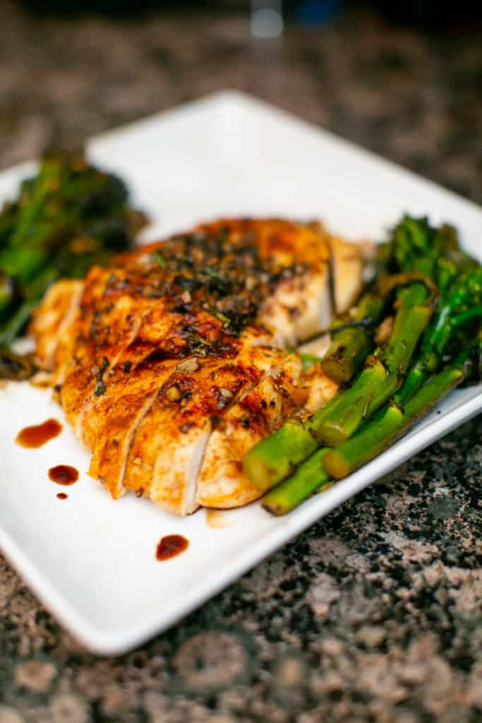 Oven baked chicken breast served with asparagus