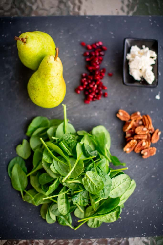 Ingredients for pear and pomegranate salad prepped over a black cutting board