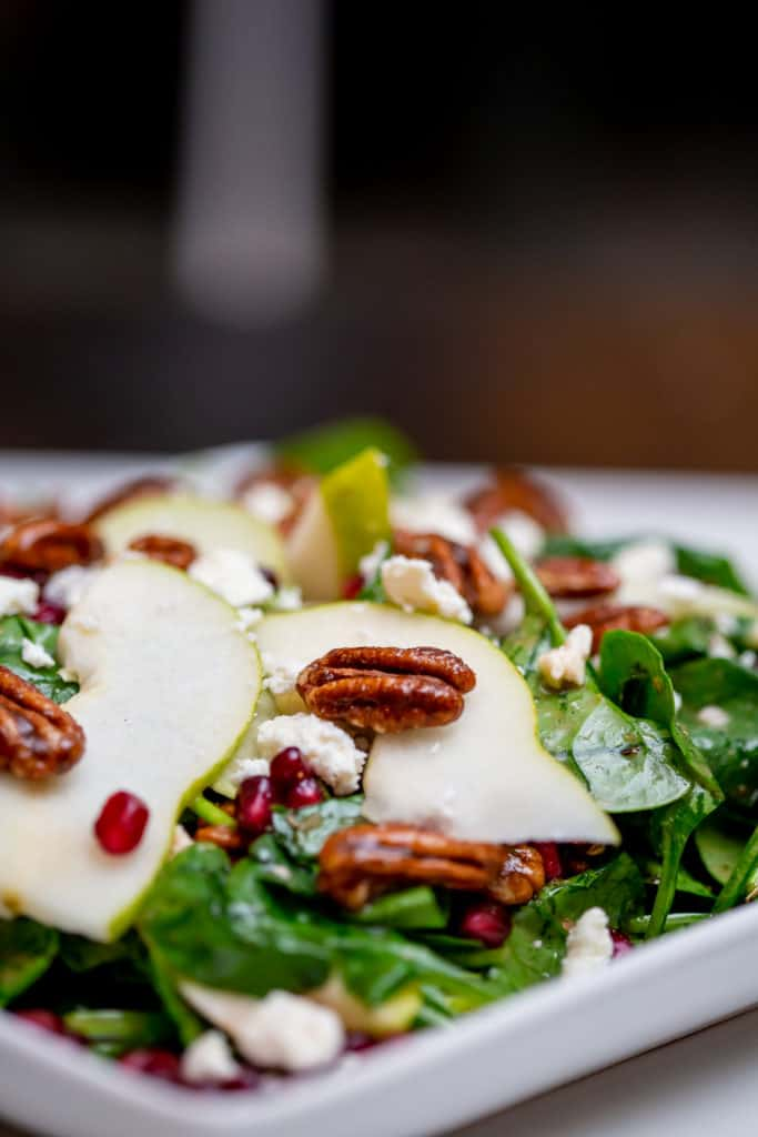 Pear and pomegranate salad topped with pecan nuts