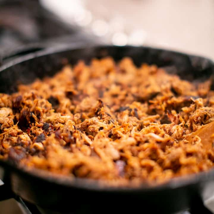 Pork carnitas cooked in a pan on high heat