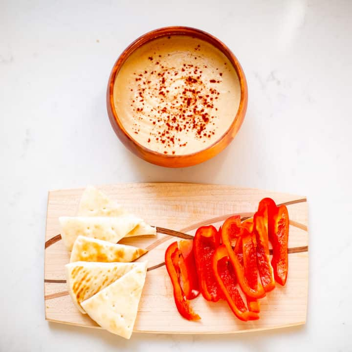Hummus paired with pita bread and bell peppers