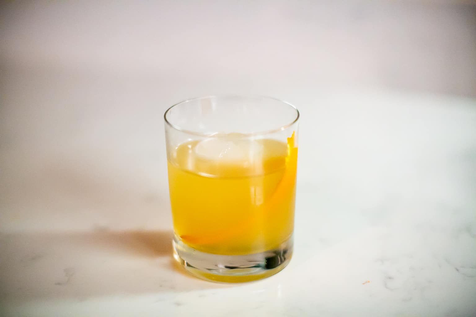 A glass of smoked tequila cocktail with lemon peel and ice