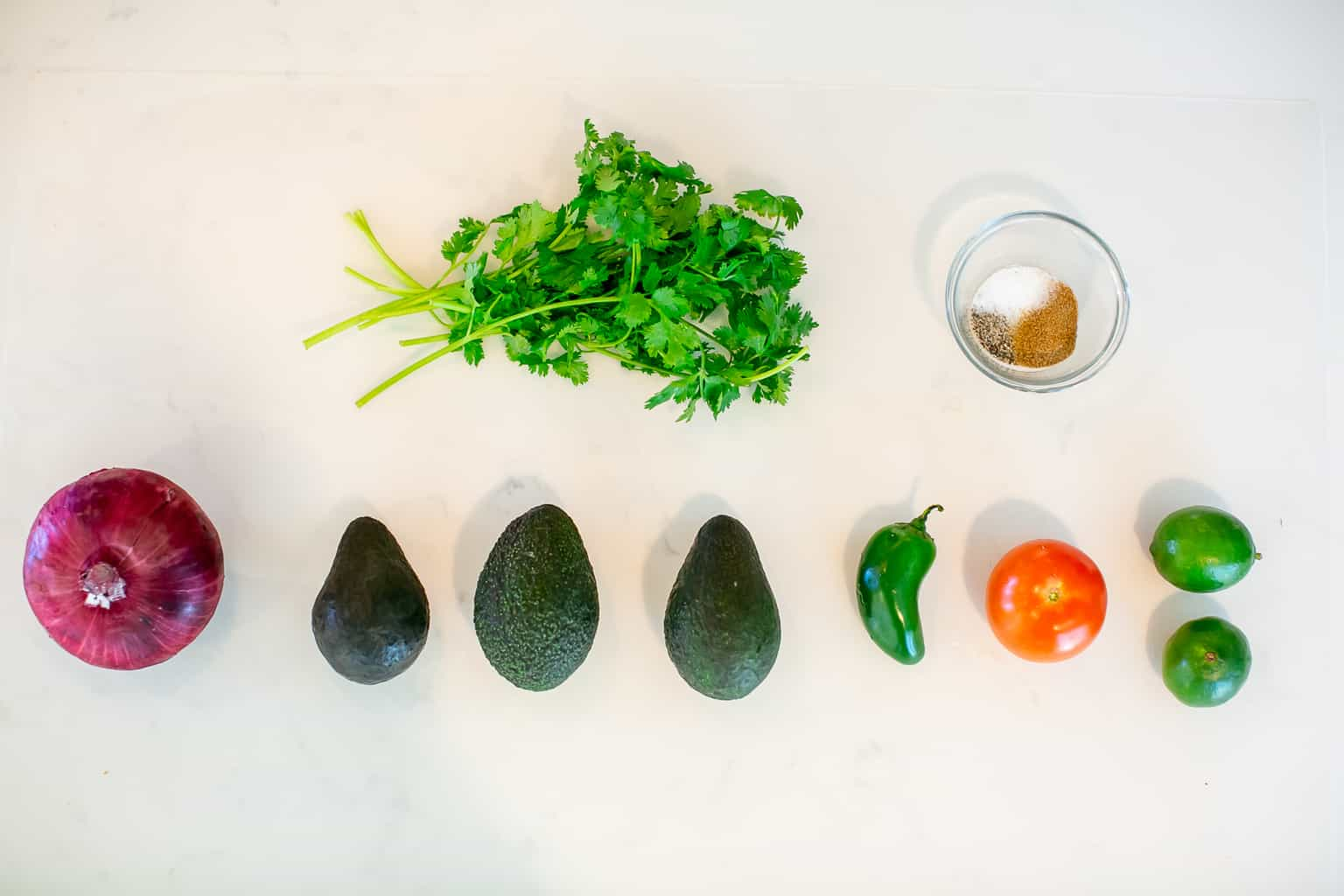 Flat lay image of ingredients needed to make spicy guacamole