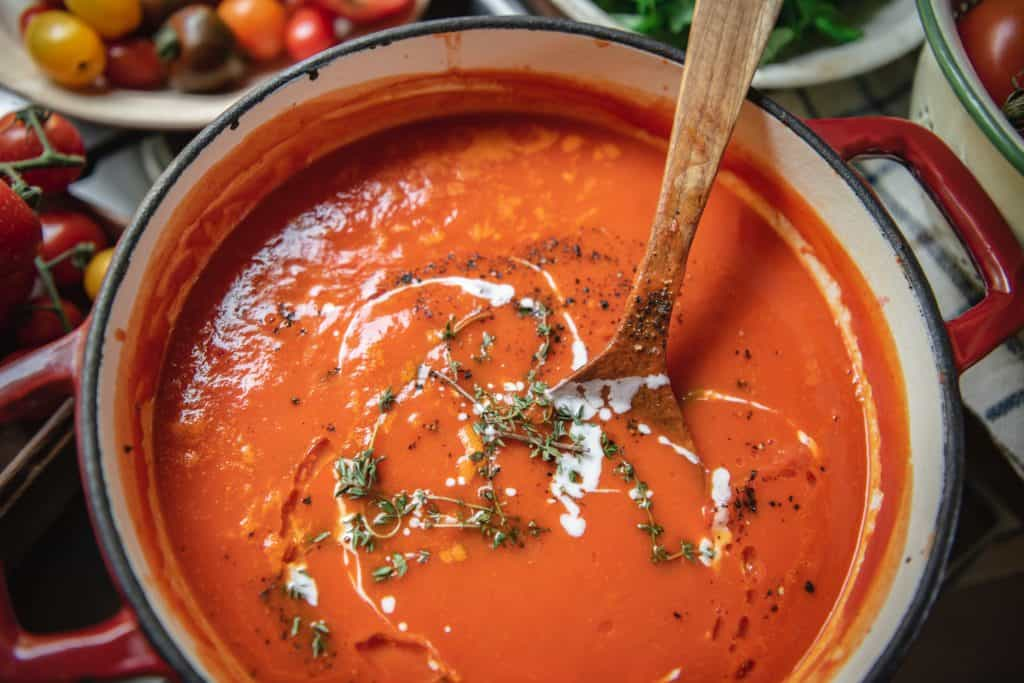 Stirring tomato soup in a pot on the stovetop