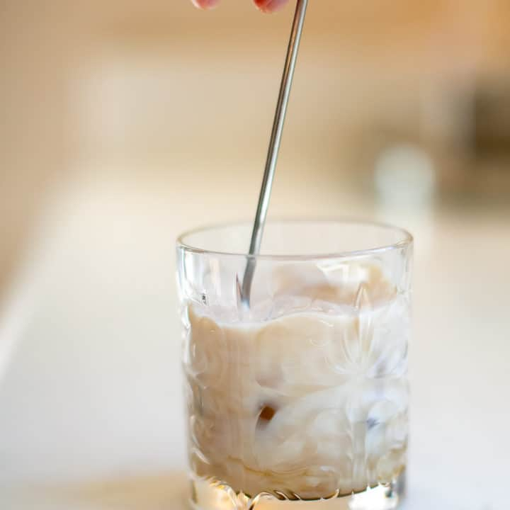 Man stirring white Russian cocktail