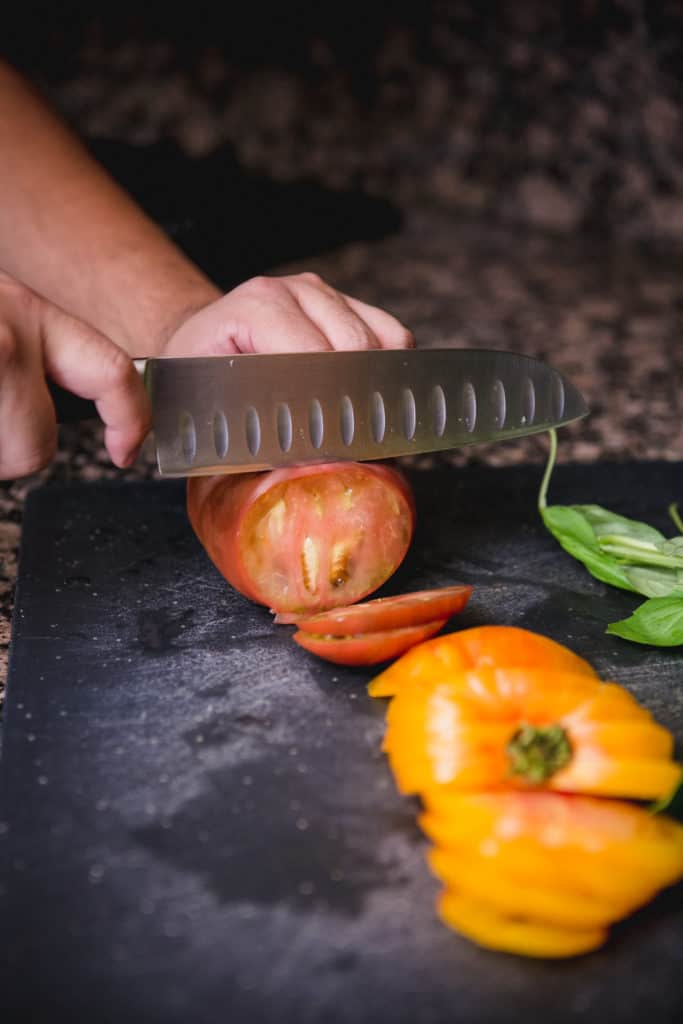 Slicing heirloom tomatoes with a chef's knife for a caprese salad