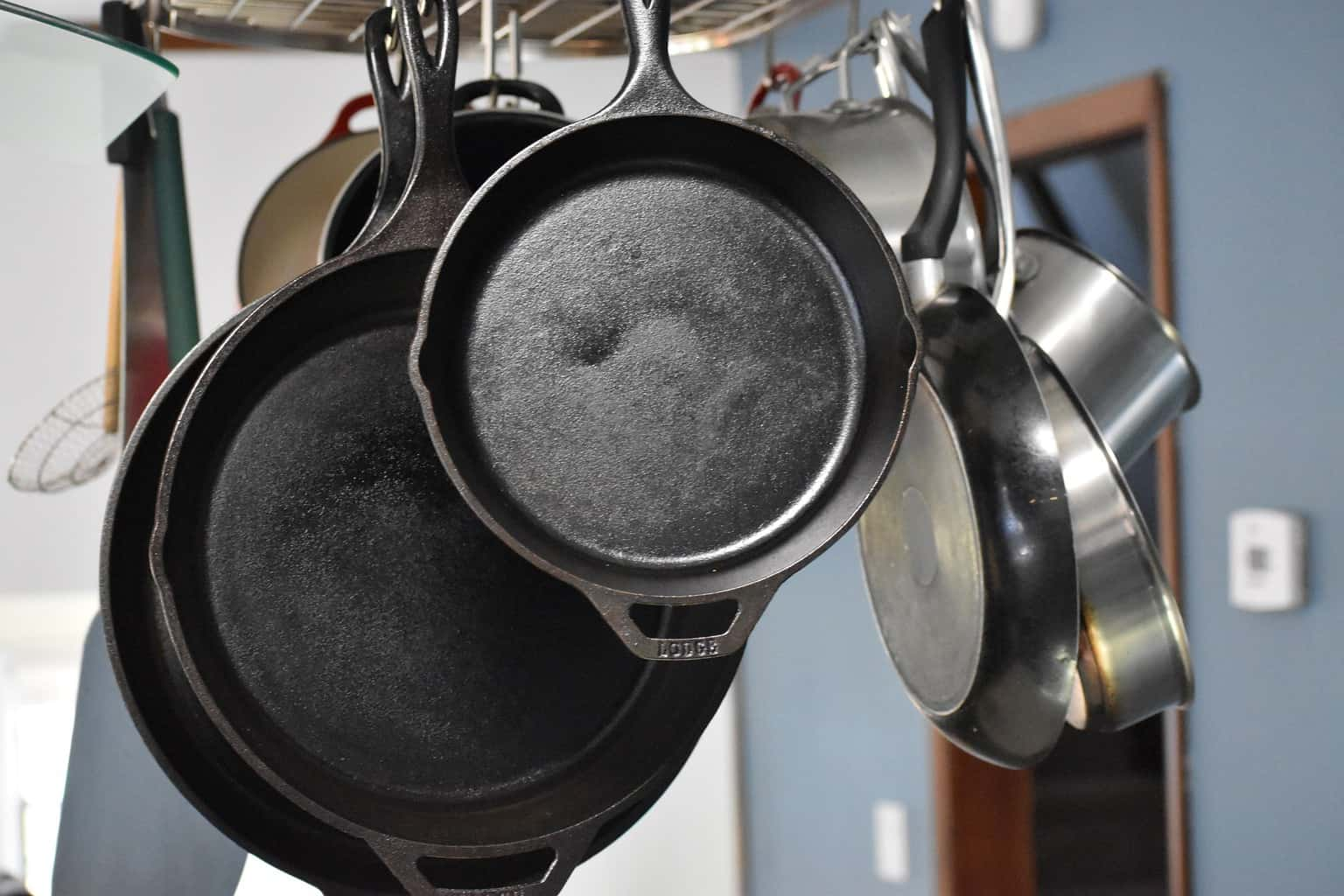 Cast iron pans and stainless steel pans hanging on a rail