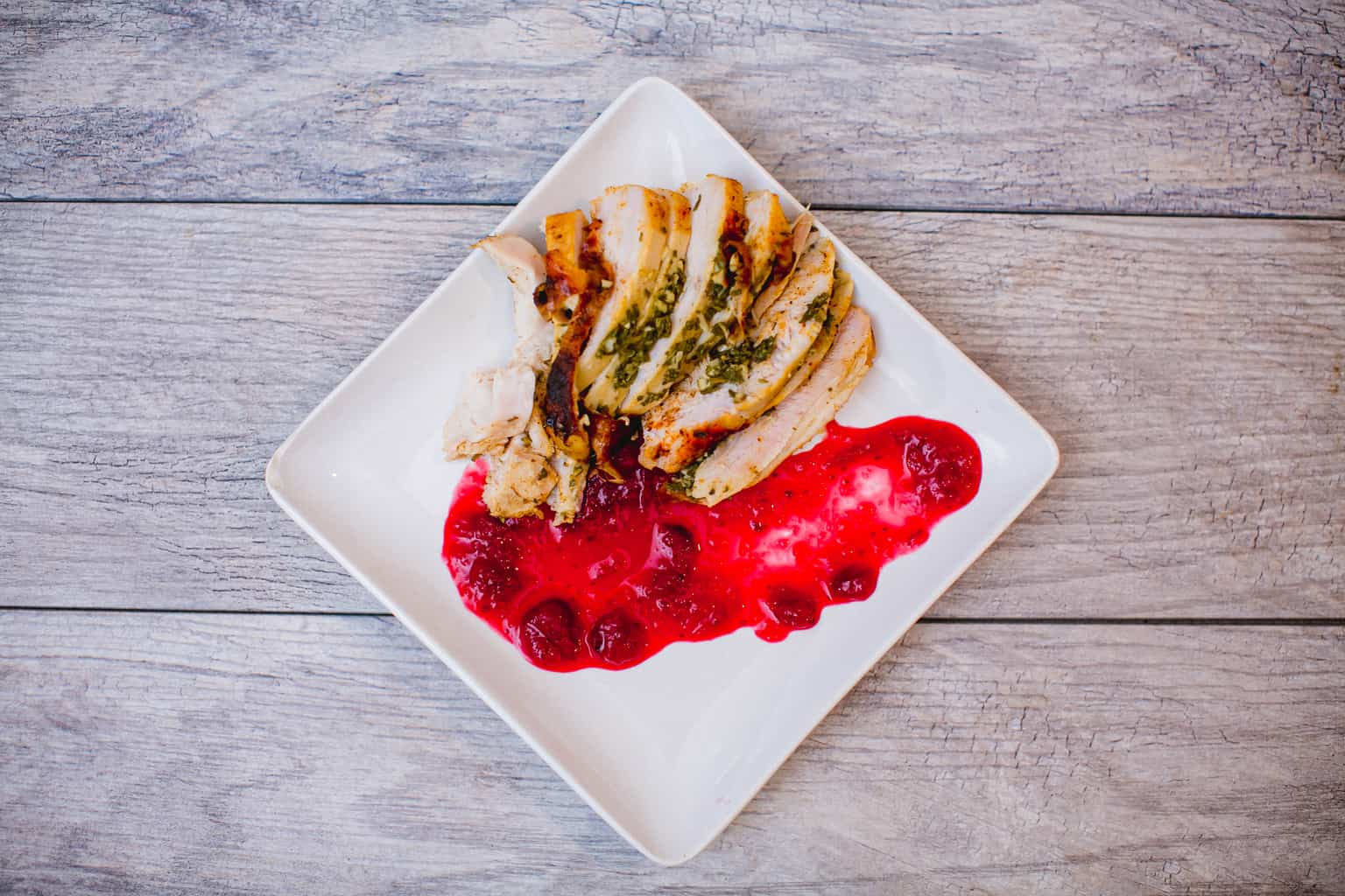A plate of oven roasted turkey breast paired with cranberry sauce