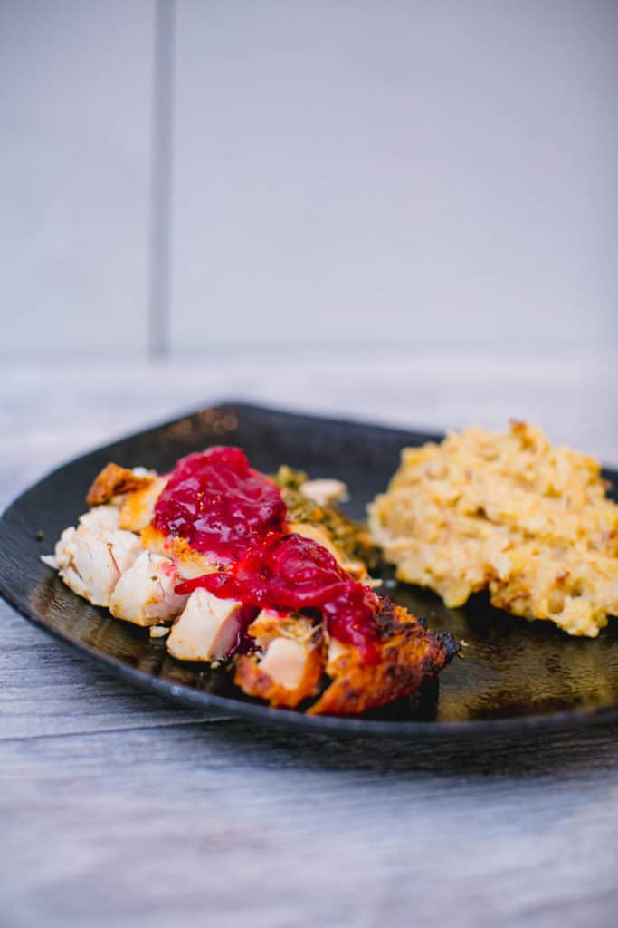 A plate of oven roasted turkey topped with cranberry sauce and paired with a side dish
