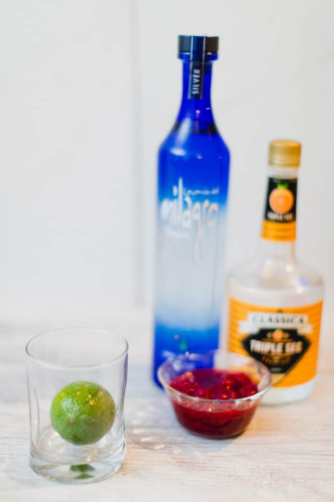 A lime, cranberries, tequila, and triple sec laid out on a table