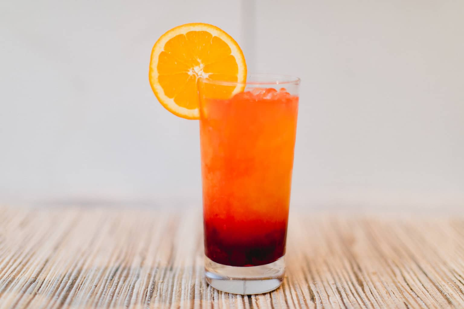 A cold glass of cranberry tequila sunrise cocktail