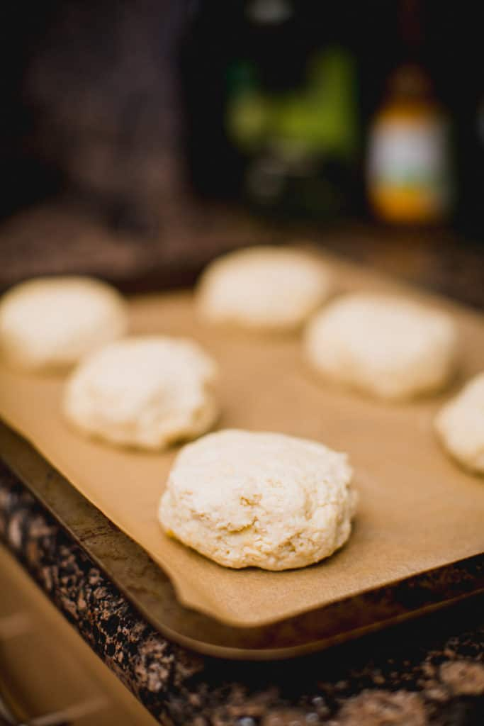 Prepared cheesy biscuit dough lined up in a tray about to go in the oven