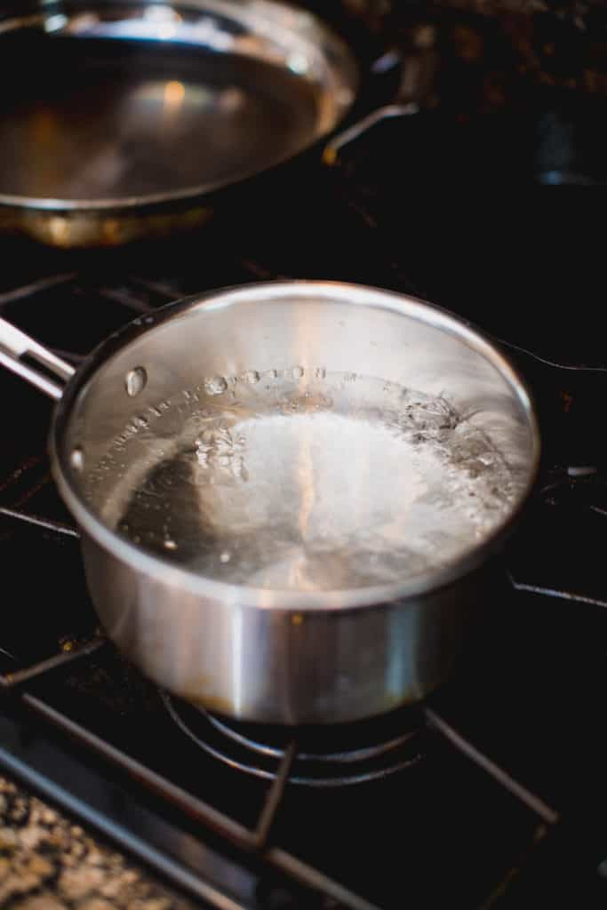 Water being boiled in a pot for blanching green beans