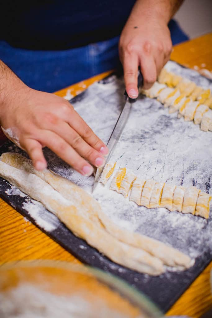 Person cutting logs of dough to make gnocchi