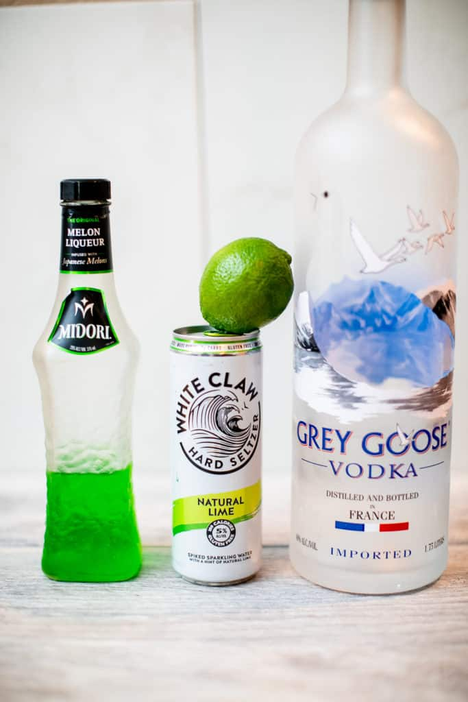 A bottle of Midori, White Claw seltzer, lime and vodka placed together on a table