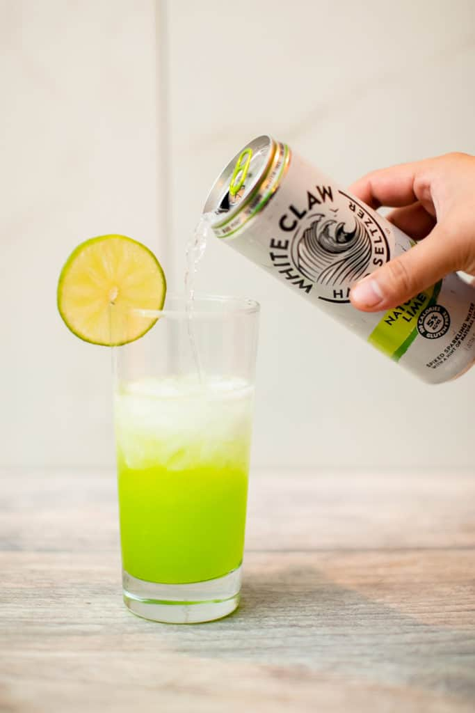 Hand pouring a can of White Claw seltzer on a glass mixture that has a slice of lemon on its rim