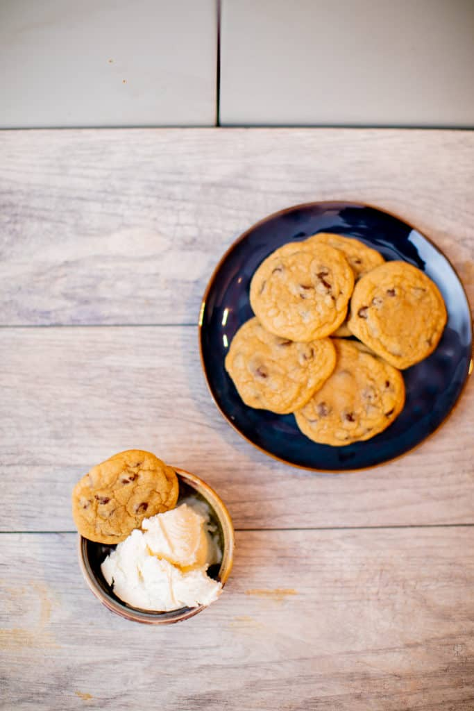 A plate full of homemade chewy chocolate chip cookies with a bowl of vanilla ice cream