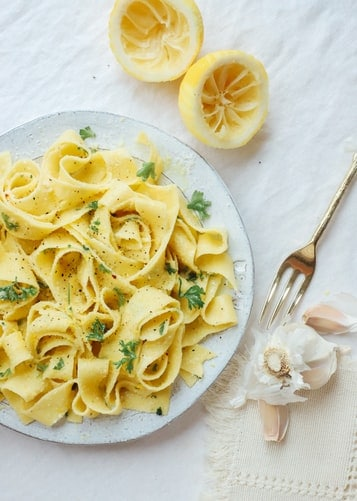 Prepared lemon and capers pasta sauce recipe on a plate with squeezed lemons and garlic on the side