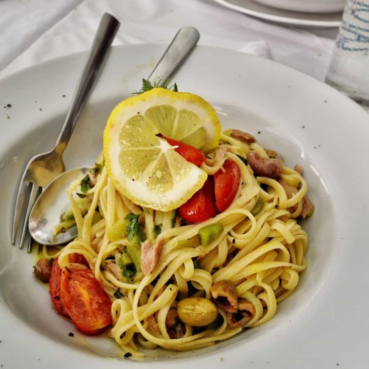 Prepared lemon and capers pasta sauce recipe on a plate with spoon and fork