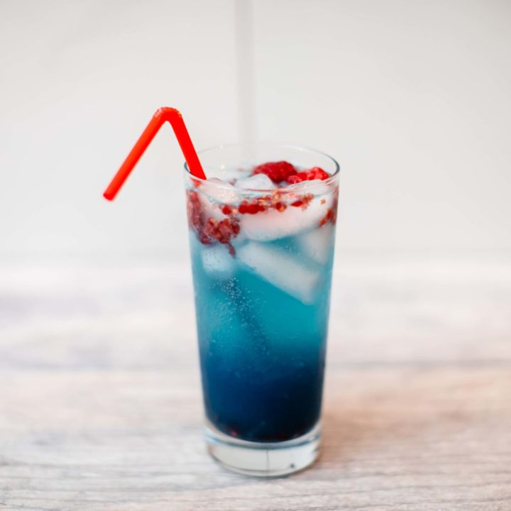 Sour raspberry white claw cocktail with rum in a tall glass with a red bendy straw placed on a table