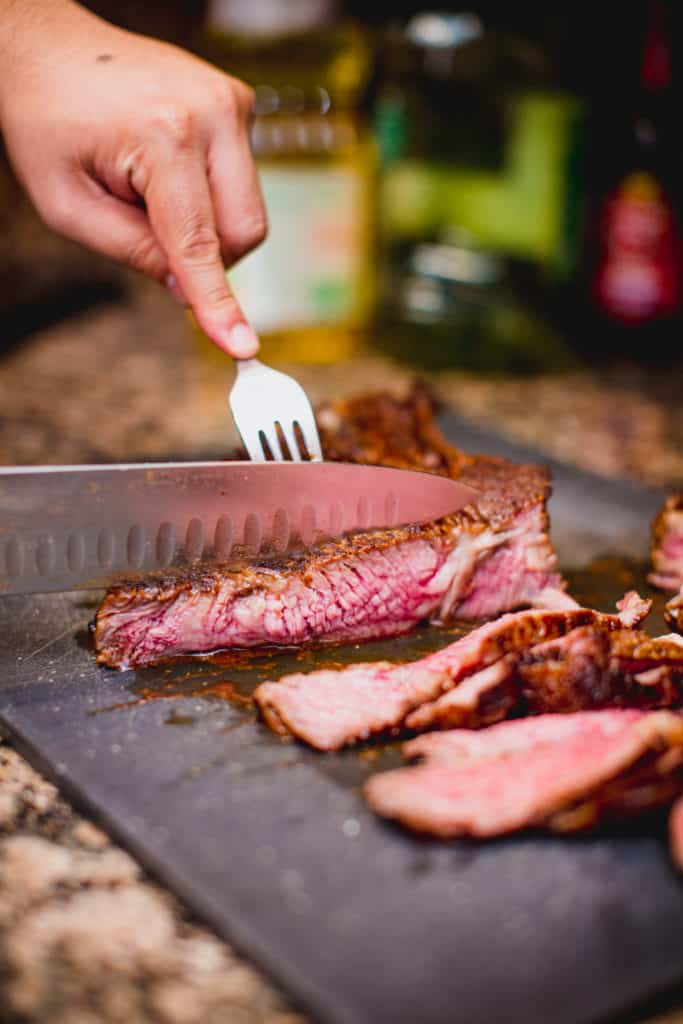 Person cutting a cooked steak with knife and fork