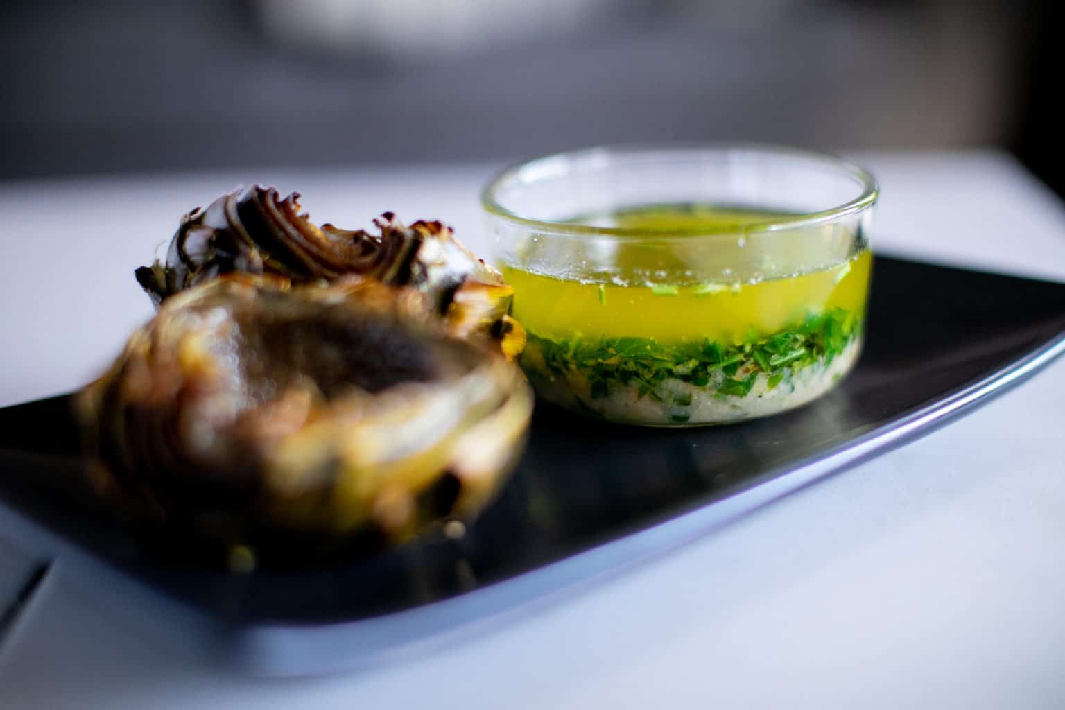 Roasted artichokes on a plate with lemon garlic butter sauce