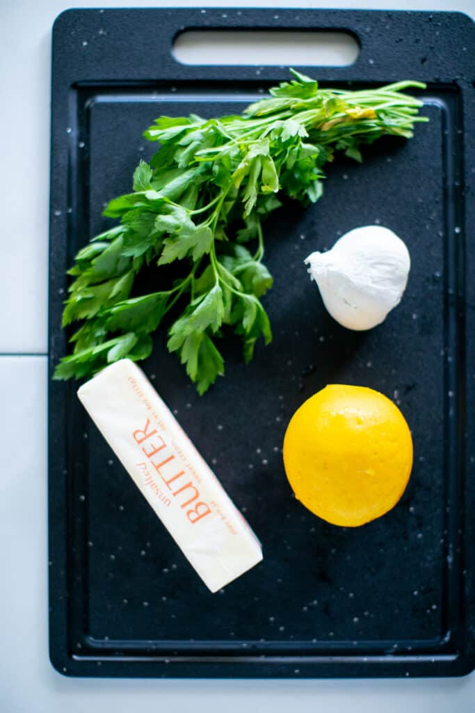 Parsley, lemon, butter and garlic on a cutting board