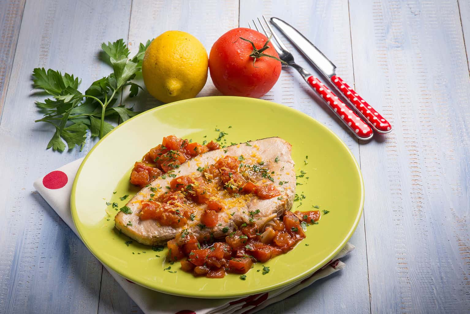 Swordfish with fresh tomatoes and grated lemon peel on a plate with a fork and knife next to it