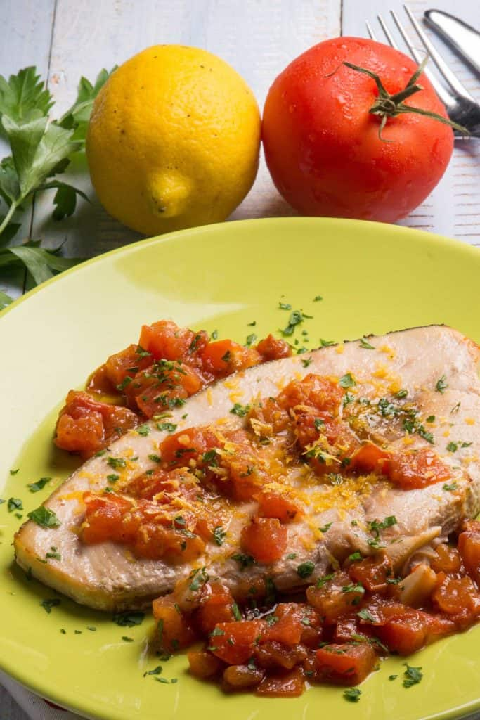 Swordfish with fresh tomatoes and grated lemon peel on a plate