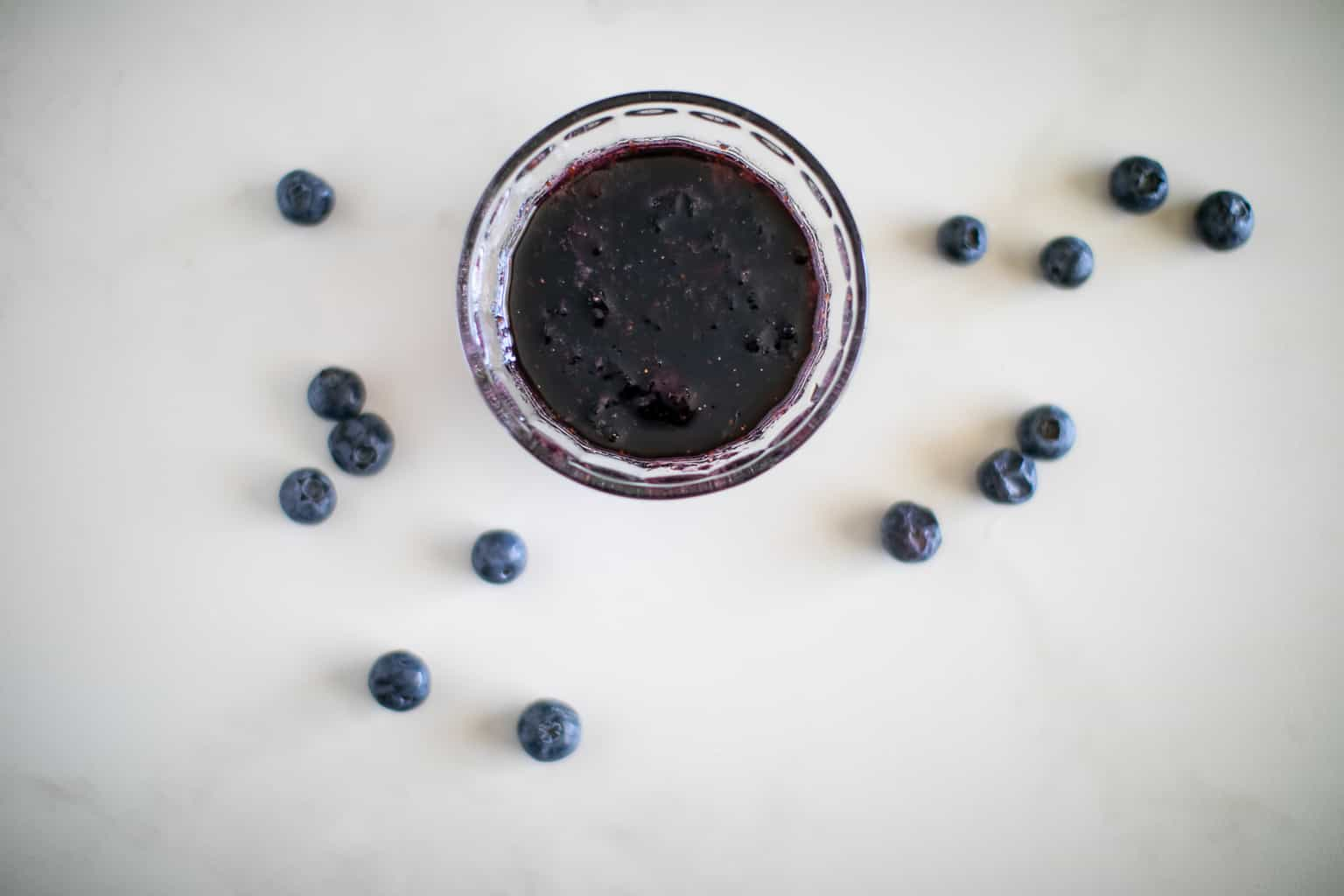 Prepared blueberry syrup in a clear bowl