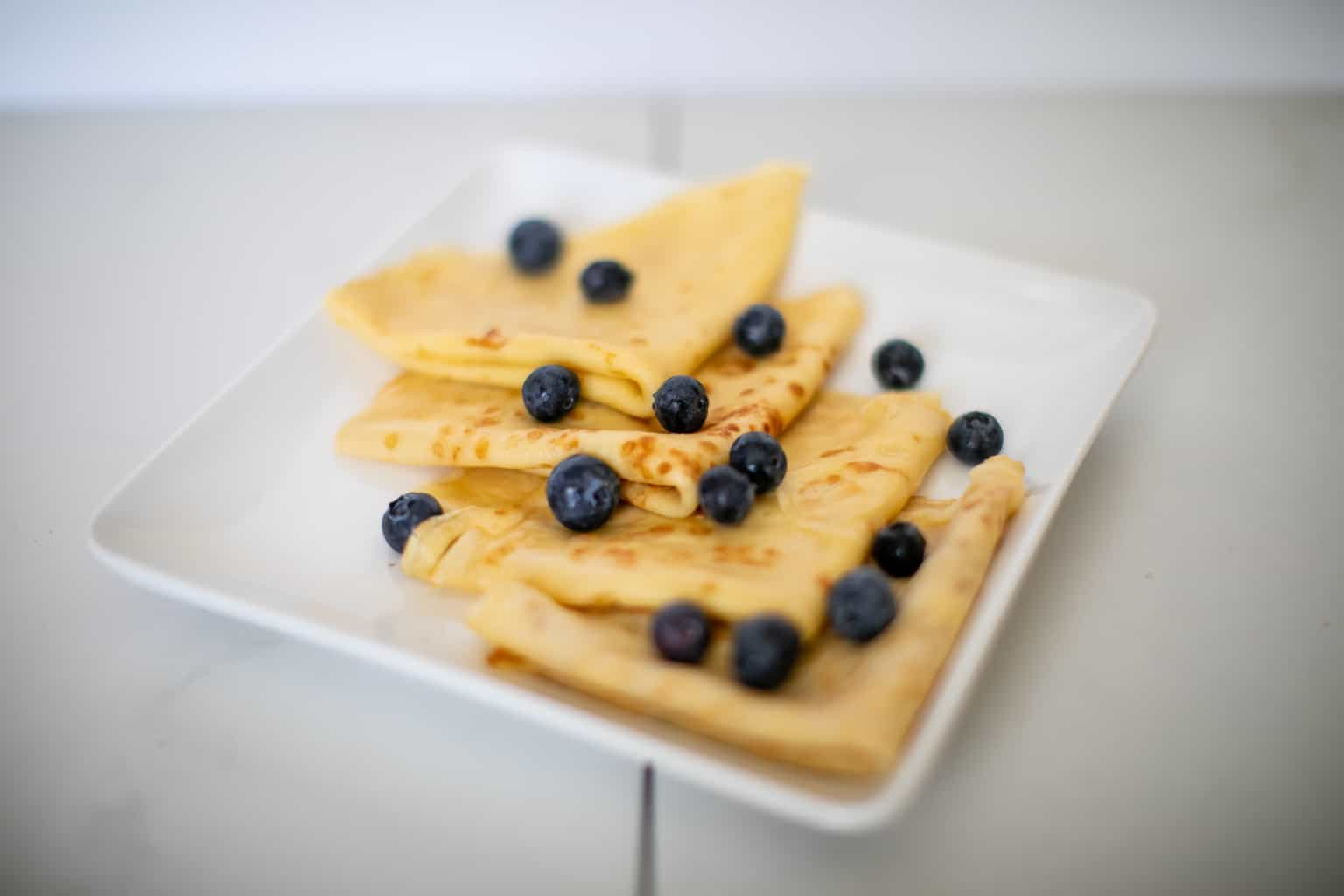 Simple french crepes recipe topped with blueberries on a plate