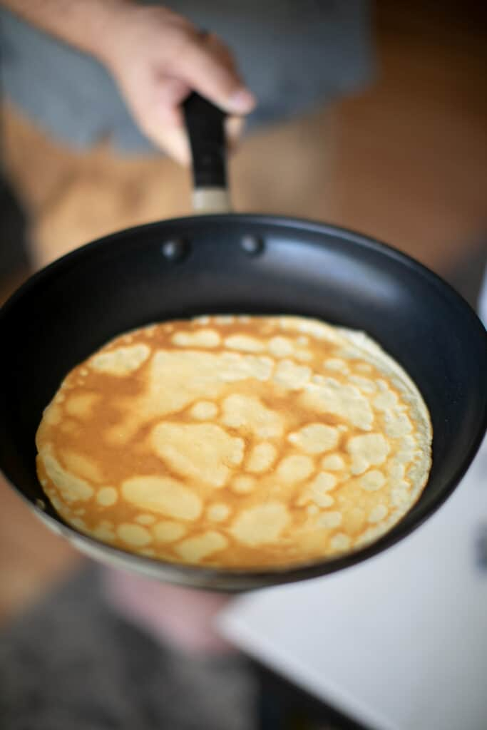 French crepe being cooked in a cast iron pan