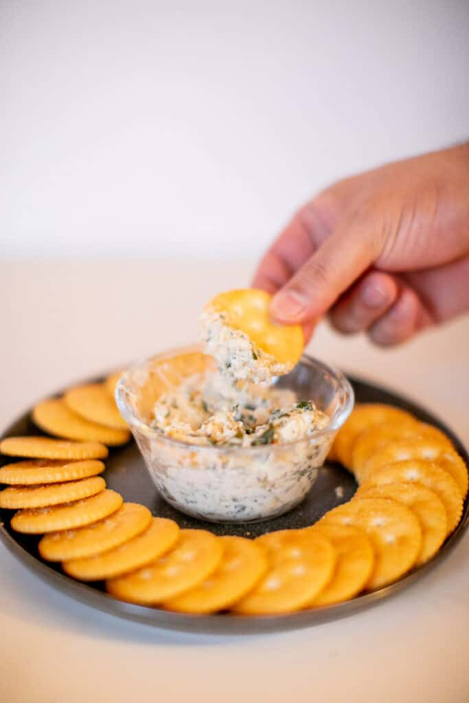A cracker being dipped in a spinach artichoke dip