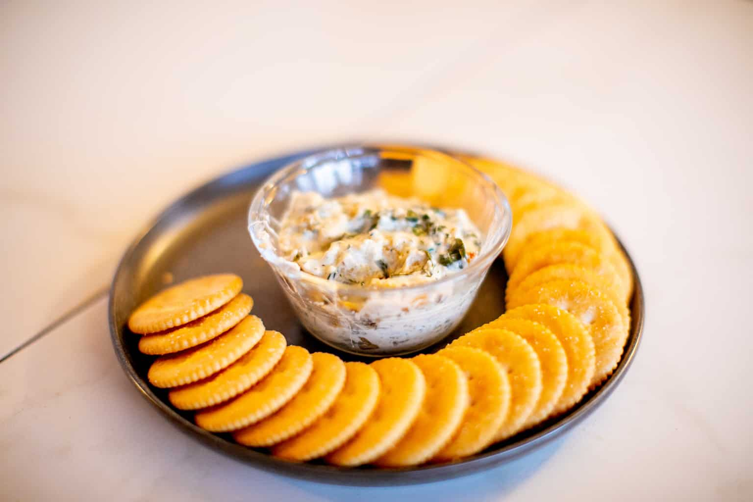 Baked spinach artichoke dip recipe prepared in a bowl with a plate full of crackers