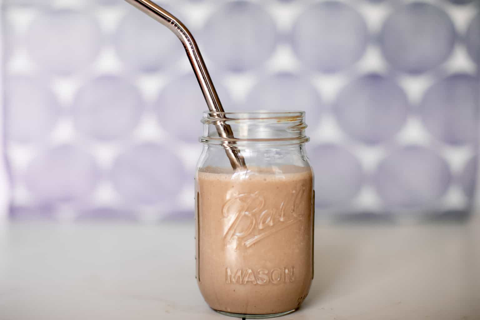 Prepared chocolate peanut butter banana smoothie recipe in a mason jar