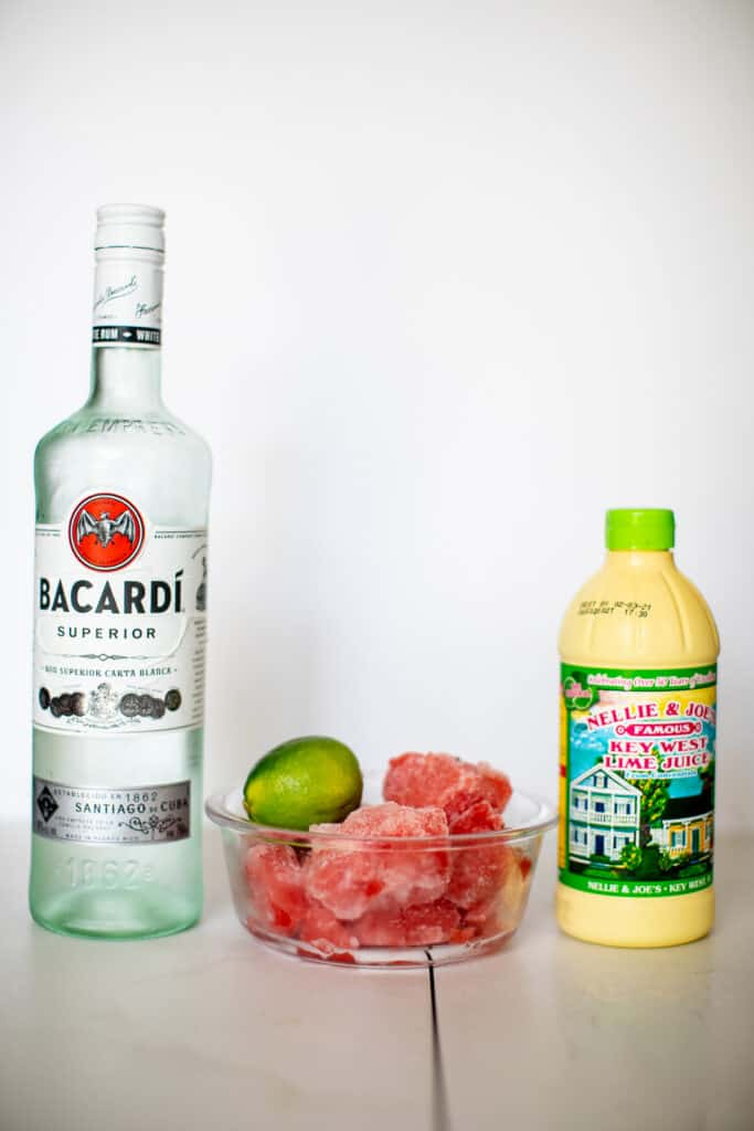 Bottle of Bacardi. bottle of key lime juice and frozen watermelon placed in a table