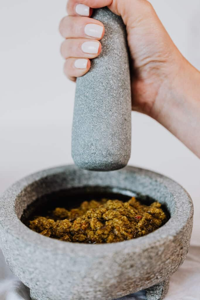 Woman using a mortar and pestle to grind an oil based sauce