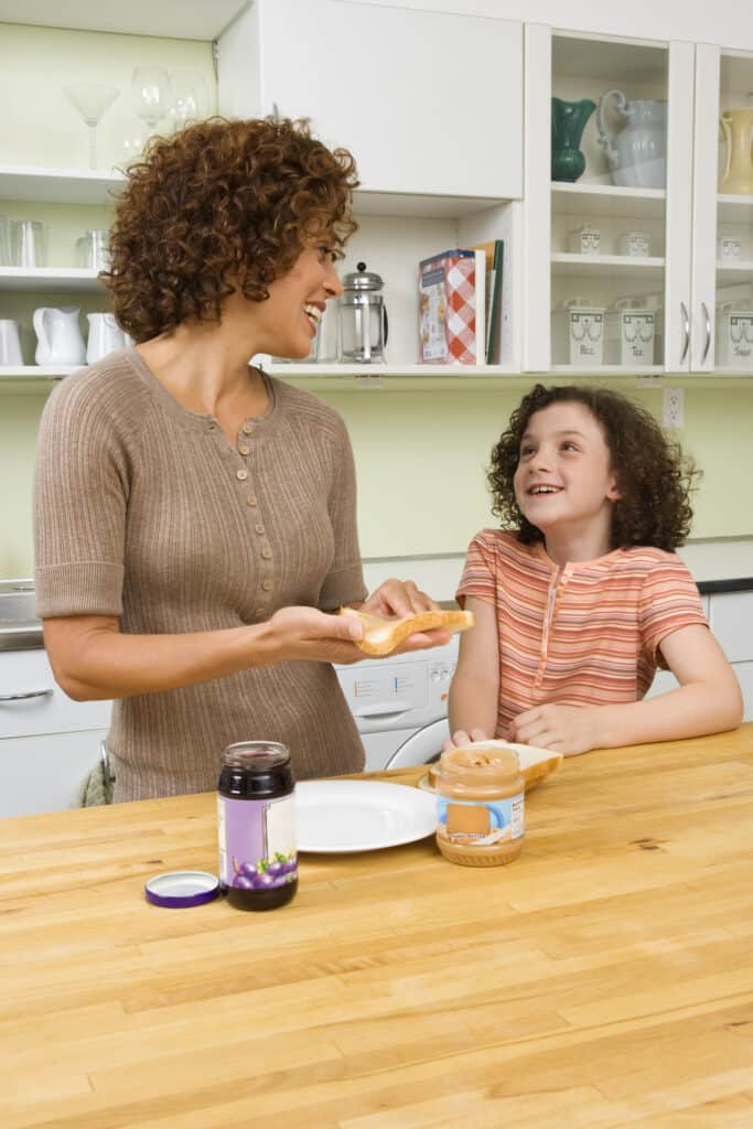 Mom and daughter making a peanut butter and jelly sandwich