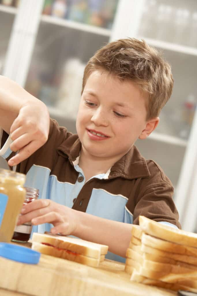 Young boy making a peanut butter and jelly sandwich