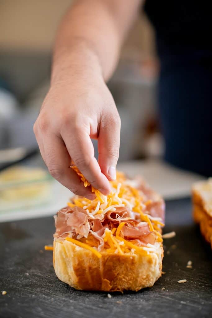 Person putting cheese on top of aged ham on a piece of bread