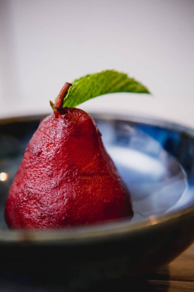 Mulled wine poached pear in a blue bowl