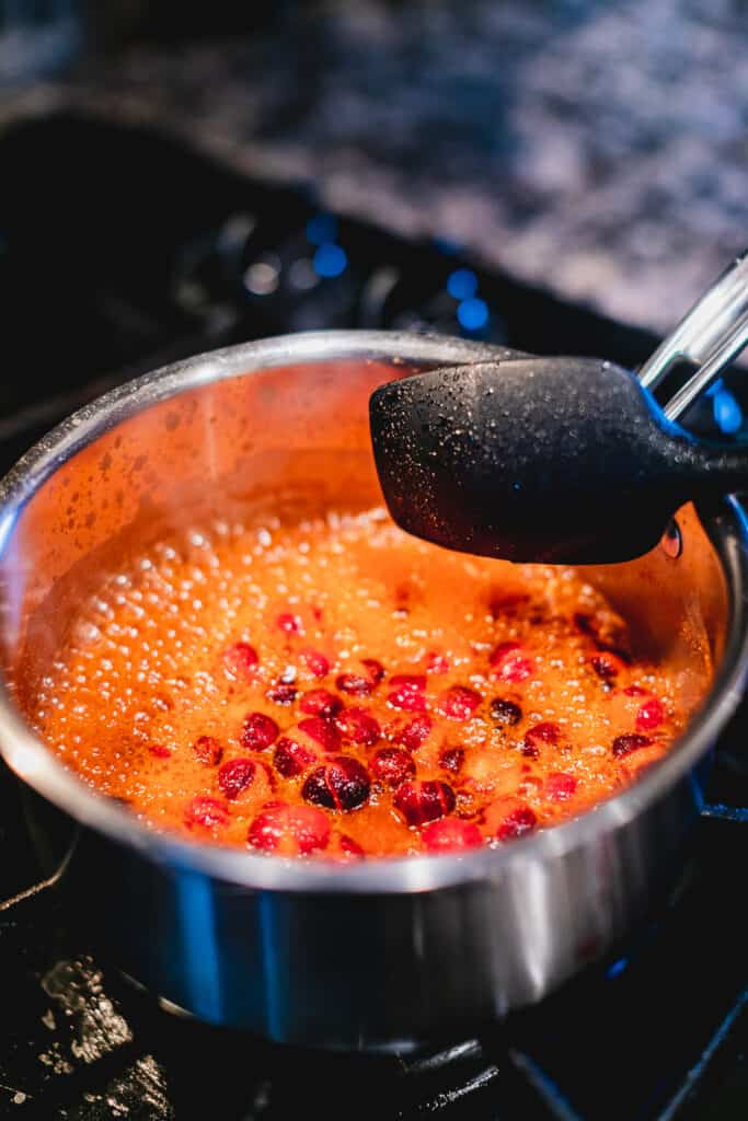 Cranberries boiling in a pot on the stove